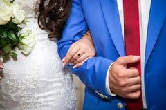 Handen met trouwringen en boeket Stock Afbeeldingen