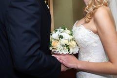 Handen met trouwringen en boeket Royalty-vrije Stock Afbeelding