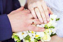 Handen met trouwringen en boeket Stock Foto