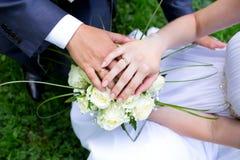 Handen met verlovingsringen op bruids boeket Stock Foto