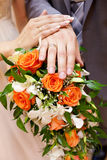 Handen met verlovingsringen op bruids boeket Royalty-vrije Stock Foto