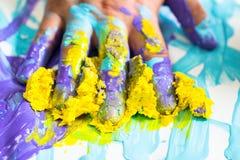 Handen och fingret som är smutsiga med lilor och guling, målar Royaltyfria Bilder