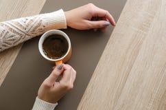 Handen op bureau met kop van koffie Royalty-vrije Stock Foto
