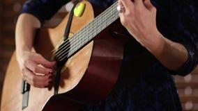 Handen op de koorden van een akoestische gitaar Close-up Een meisje in een blauwe kleding voltooit het spel op een muzikaal instr stock footage