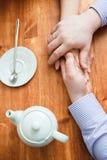 Handen op de lijst in koffie Stock Afbeelding