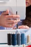 Handen op naaimachine met spoelen van kleur draden en het naaien Stock Afbeeldingen