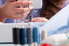 Handen op naaimachine met spoelen van kleur draden en het naaien Royalty-vrije Stock Afbeeldingen