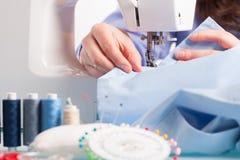 Handen op naaimachine met spoelen van kleur draden en het naaien Royalty-vrije Stock Afbeelding