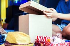 Handen open doos en bloem, klok, hoed rond de doos stock foto