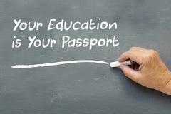 Handen på en svart tavla med meddelandet din utbildning är din pas Royaltyfria Foton