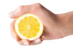 Handen pressar citronjuice på en vit bakgrund royaltyfri bild