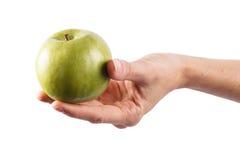 Handen rymmer äpplet Arkivfoto