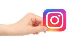 Handen rymmer den nya Instagram logoen royaltyfria foton