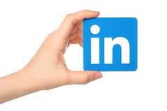 Handen rymmer det Linkedin logotecknet utskrivavet på papper på vit bakgrund royaltyfri foto