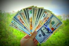 Handen rymmer dollar och euro royaltyfri fotografi