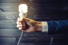 Handen rymmer en glödande ljus kula Idérik idé i affär Royaltyfri Bild