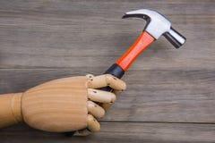 Handen rymmer en hammare Arkivbild