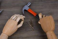 Handen rymmer en hammare Arkivfoto