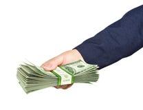 Handen rymmer en packe av dollar på blå bakgrund Fotografering för Bildbyråer