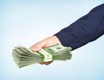 Handen rymmer en packe av dollar på blå bakgrund Arkivbilder