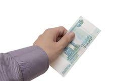 Handen rymmer en sedel av 1000 rubles Arkivbilder