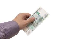 Handen rymmer en sedel av 1000 rubles Royaltyfri Bild