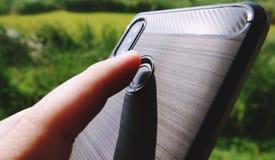 Handen rymmer en svart telefon, och pekfingret trycker på fingeravtryckbildläsaren för att låsa smartphonen upp arkivfoto