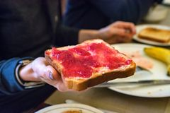Handen rymmer ett stycke av bröd med rött driftstopp Arkivbild