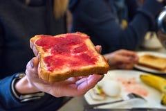 Handen rymmer ett stycke av bröd med rött driftstopp Arkivfoto