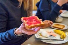 Handen rymmer ett stycke av bröd med rött driftstopp Royaltyfri Fotografi