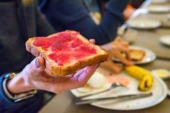 Handen rymmer ett stycke av bröd med rött driftstopp Royaltyfria Bilder