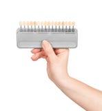 Handen rymmer färgpaletten för tänderna Arkivfoton
