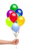Handen rymmer färgrika ballonger isolerade på vit Royaltyfri Foto