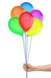 Handen rymmer färgrika ballonger isolerade på vit Arkivbilder