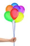 Handen rymmer färgrika ballonger isolerade på vit Fotografering för Bildbyråer