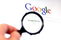 Handen rymmer förstoringsglaset mot Google homepage Arkivfoto