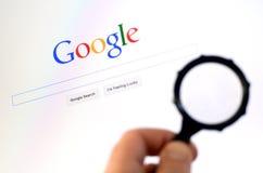 Handen rymmer förstoringsglaset mot Google homepage Royaltyfria Foton
