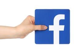 Handen rymmer facebooklogo utskrivaven på papper på vit bakgrund Royaltyfri Foto