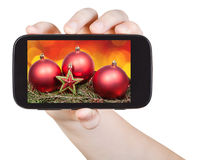 Handen rymmer handphone med Xmas-garneringar Arkivbilder