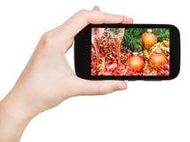 Handen rymmer handphone med Xmas-stilleben Arkivbild