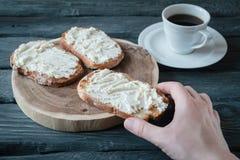 Handen rymmer hemlagad sandwiche med gräddost över en svart uppvaktar Arkivfoto