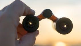 Handen rymmer kikare på solnedgång Arkivfoton