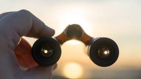 Handen rymmer kikare på solnedgång Royaltyfri Bild