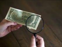 Handen rymmer lyckliga två dollar som beskådas till och med ett förstoringsglas arkivfoton