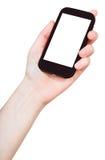 Handen rymmer mobiltelefonen isolerad Royaltyfri Fotografi