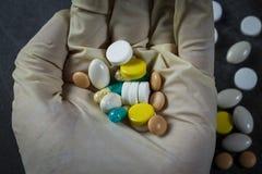 Handen rymmer några preventivpillerar över en grupp av droger Arkivfoto