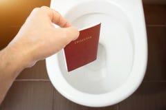 Handen rymmer passet för medborgare` s över toaletten, kastar ut hans pass Begrepp - ändring av medborgarskap, förlust av passet, royaltyfri foto