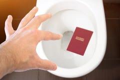 Handen rymmer passet för medborgare` s över toaletten, kastar ut hans pass Begrepp - ändring av medborgarskap, förlust av passet, royaltyfri fotografi
