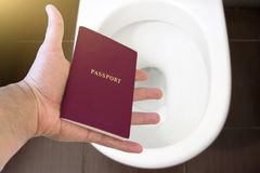 Handen rymmer passet för medborgare` s över toaletten, kastar ut hans pass Begrepp - ändring av medborgarskap, förlust av passet, arkivbild
