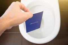 Handen rymmer passet för medborgare` s över toaletten, kastar ut hans pass Begrepp - ändring av medborgarskap, förlust av passet, royaltyfria bilder